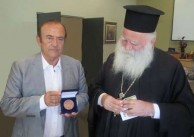 Metropolitan Seraphim of Kythera and Antikythera, admiring the Kytherian Medal of Honour