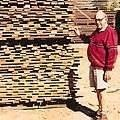 Brinos Notaras in front of a stack of blackbutt boards, drying.