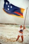 George C Poulos gambolling in the surf at Bondi Beach with the official Bondi Beach Flag - his own design
