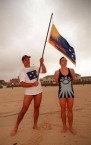 George C Poulos holding the official Rising Sun Flag of Bondi Beach over a life-saver wearing one of the original Bondi Beach Rising Sun Life Saver's uniforms from the 1920's and 1930's